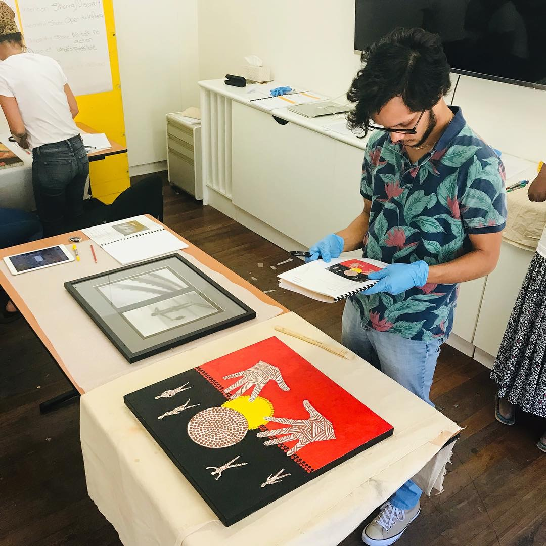 Kuberan Muir undertaking an artwork condition report at ART ON THE MOVE. Photo: Ron Bradfield Jnr.